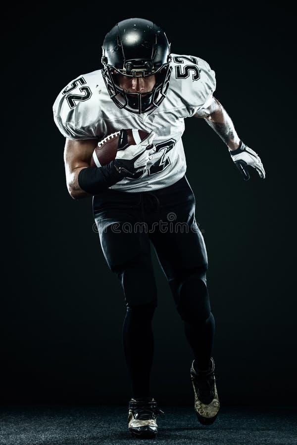 Futbolu amerykańskiego sportowa gracz w hełmie odizolowywał bieg w akcji na czarnym tle Sporta i motywacji tapeta zdjęcie stock