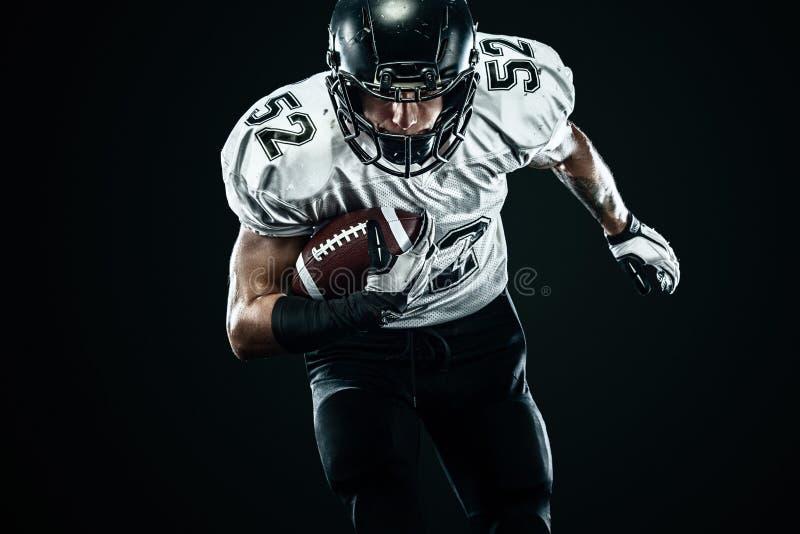 Futbolu amerykańskiego sportowa gracz w hełmie odizolowywał bieg w akcji na czarnym tle Sporta i motywacji tapeta zdjęcie royalty free