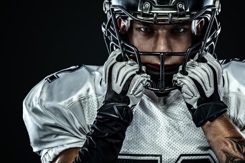Futbolu amerykańskiego sportowa gracz w hełmie odizolowywającym na czarnym tle Sporta i motywacji tapeta fotografia royalty free