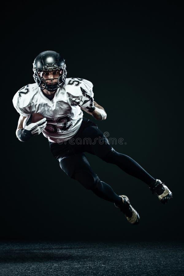 Futbolu amerykańskiego sportowa gracz w hełmie odizolowywającym na czarnym tle Sporta i motywacji tapeta zdjęcie stock