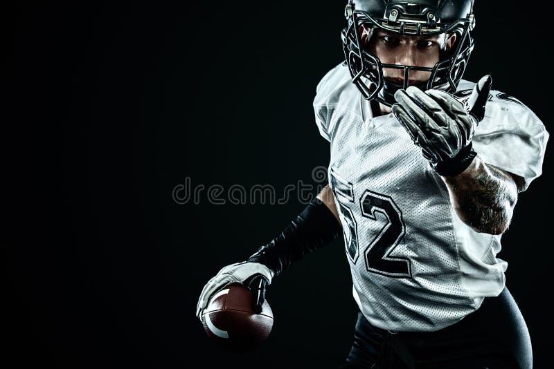 Futbolu amerykańskiego sportowa gracz w hełmie odizolowywającym na czarnym tle Sporta i motywacji tapeta zdjęcia royalty free