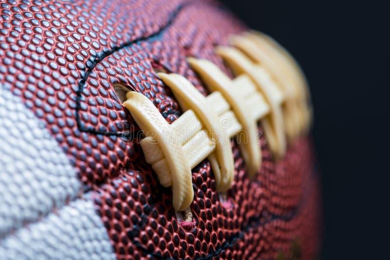 Futebol americano de couro no fundo preto fotos de stock