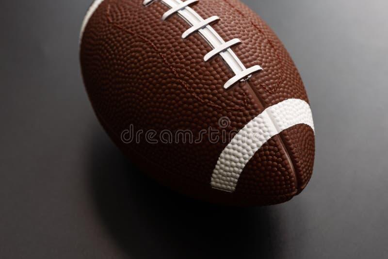 Futebol americano isolado no fundo preto Conceito do objeto do esporte imagem de stock