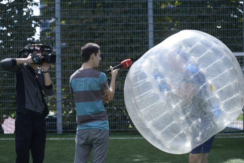 Futebol de bolhas Jornalista e cameraman entrevistando um homem em uma bolha imagem de stock royalty free