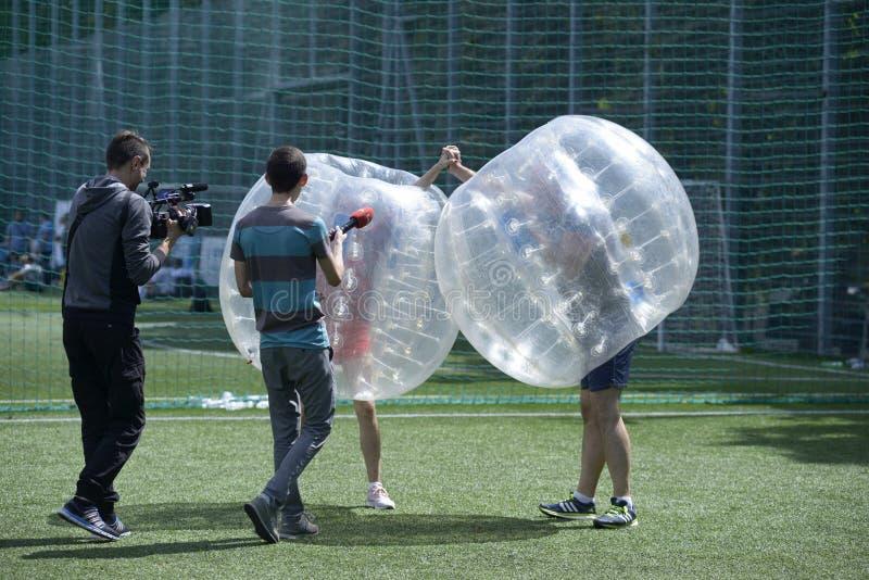 Futebol de bolhas Jornalista e cameraman entrevistando um homem em uma bolha imagens de stock royalty free