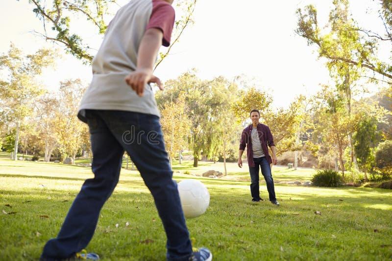 Futebol de retrocesso do menino da criança de sete anos a seu paizinho no parque, colheita imagem de stock