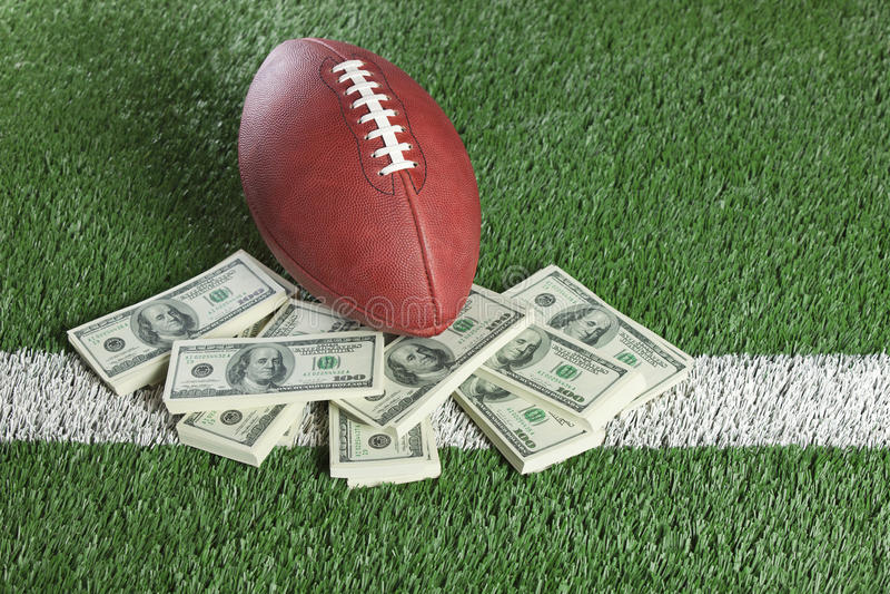 Futebol do NFL no campo com uma pilha de dinheiro foto de stock