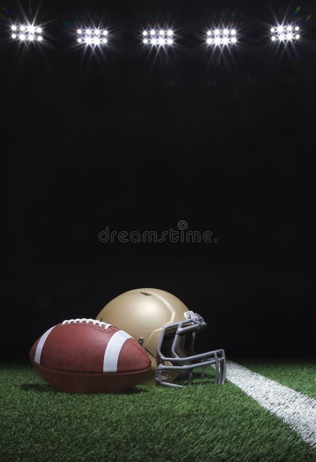 Futebol e capacete no campo de grama abaixo das luzes de estádio à noite foto de stock