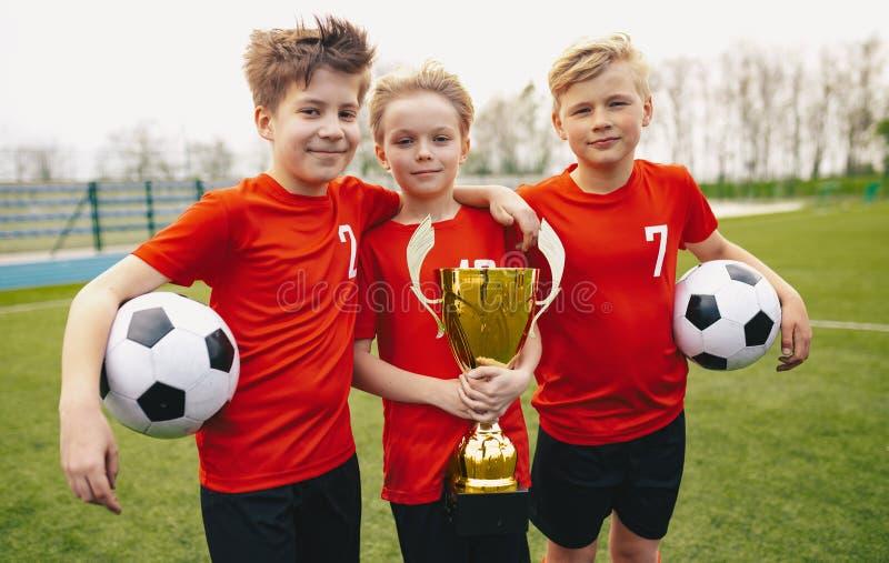 Futebol feliz Team Players Holding Trophy dos esportes Vencedores do competiam do futebol da juventude imagem de stock royalty free