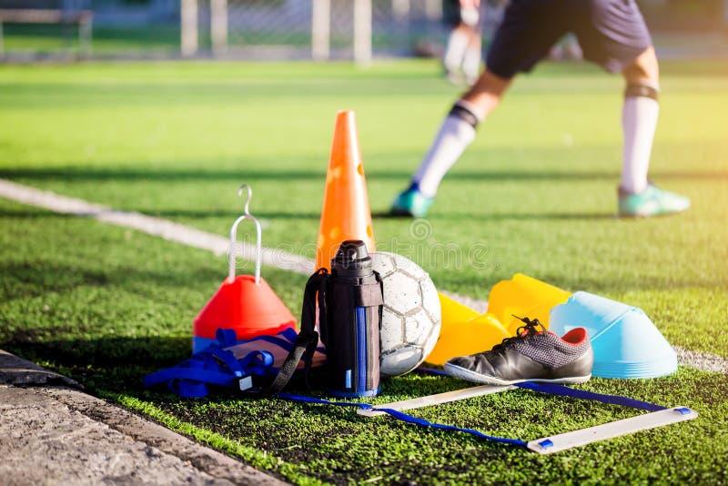 Futebol, garrafa fresca, sapatas vermelhas pretas dos esportes e treinamento do futebol foto de stock royalty free
