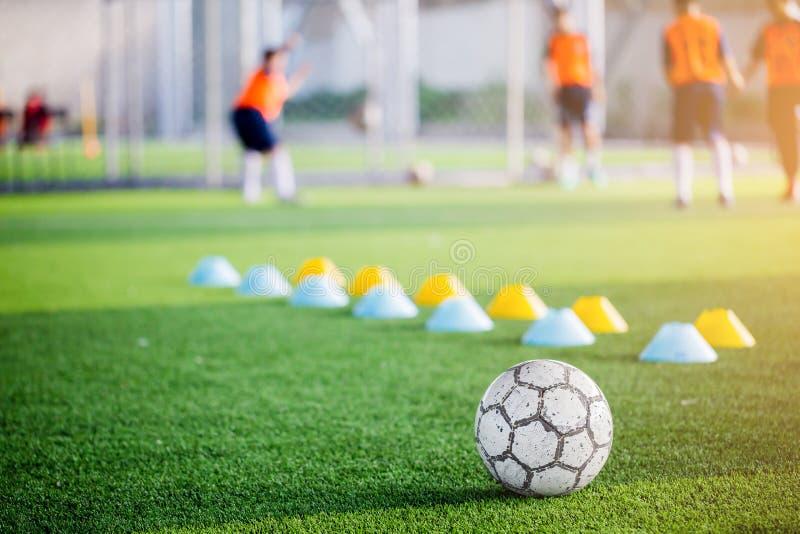 Futebol no relvado artificial verde com o obscuro de cones do fabricante e imagem de stock
