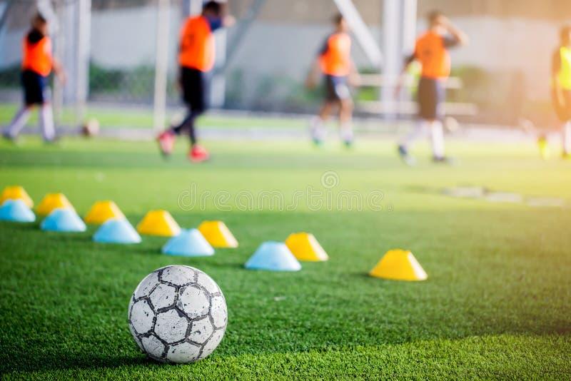 Futebol no relvado artificial verde com o obscuro de cones do fabricante e imagem de stock royalty free