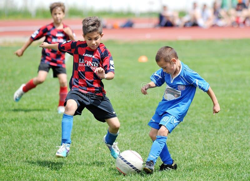 Futebol ou futebol do jogo dos meninos das crianças pequenas fotografia de stock