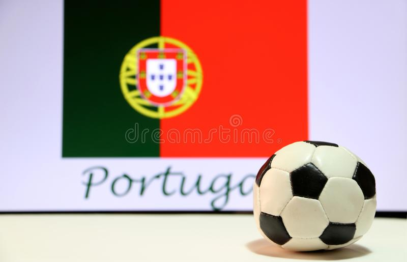 Futebol pequeno no assoalho branco e na bandeira portuguesa da nação com o texto do fundo de Portugal fotos de stock