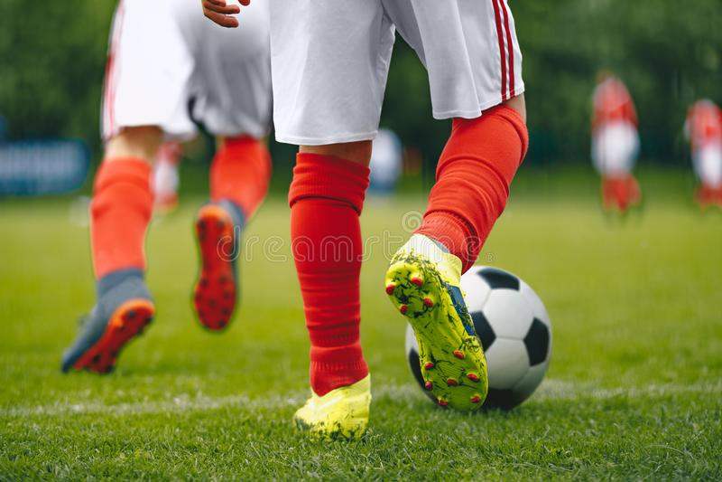 Futebol/futebol que corre com a bola Ideia do close-up da bola de futebol e do pé do jogador imagem de stock