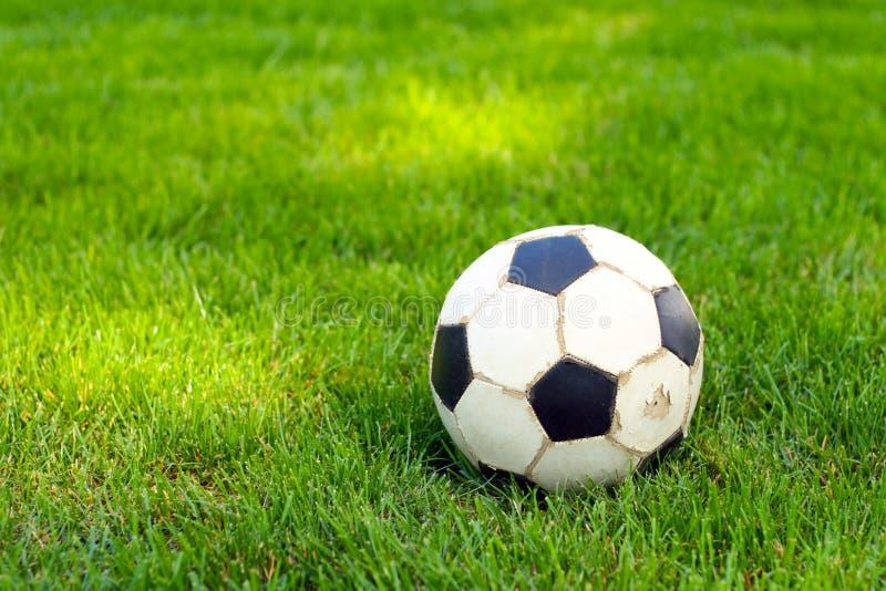 Futebol velho, bola de futebol na grama imagem de stock royalty free