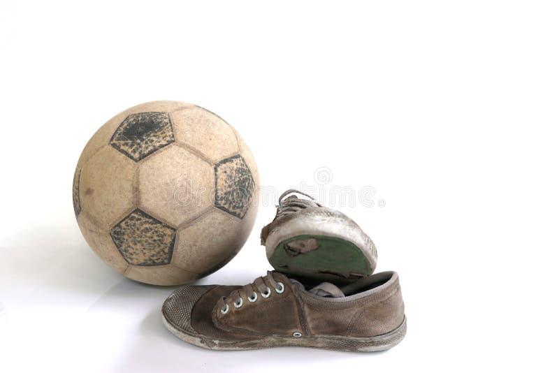 Futebol velho e sapatas velhas isolados fotos de stock royalty free