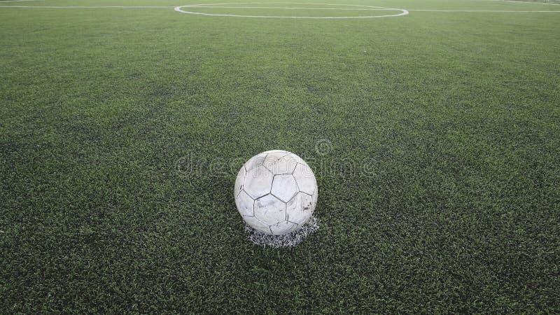 Futebol velho na grama falsificada fotos de stock royalty free