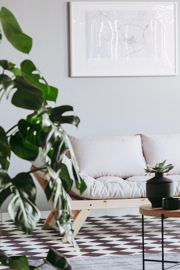 Futon escandinavo en la sala de estar beige interior con el piso blanco y negro imagen de archivo libre de regalías
