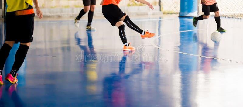 Futsal spelarefälla och att kontrollera bollen för fors till målet Fotbollspelare som slåss sig, genom att sparka bollen Inomhus  royaltyfri bild