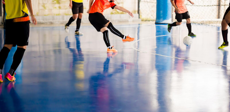 Futsal spelarefälla och att kontrollera bollen för fors till målet Fotbollspelare som slåss sig, genom att sparka bollen Inomhus  arkivfoton