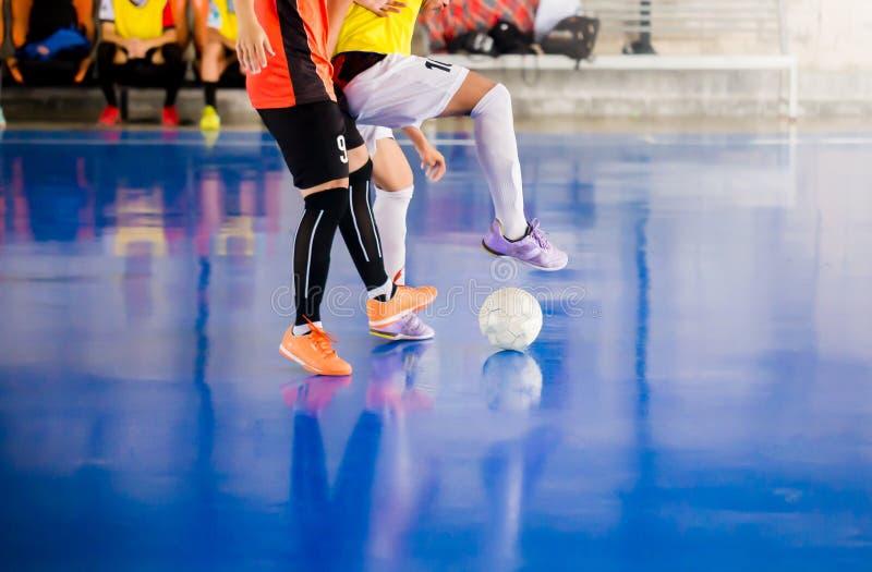 Futsal spelarefälla och att kontrollera bollen för fors till målet Fotbollspelare som slåss sig, genom att sparka bollen Inomhus  arkivbilder