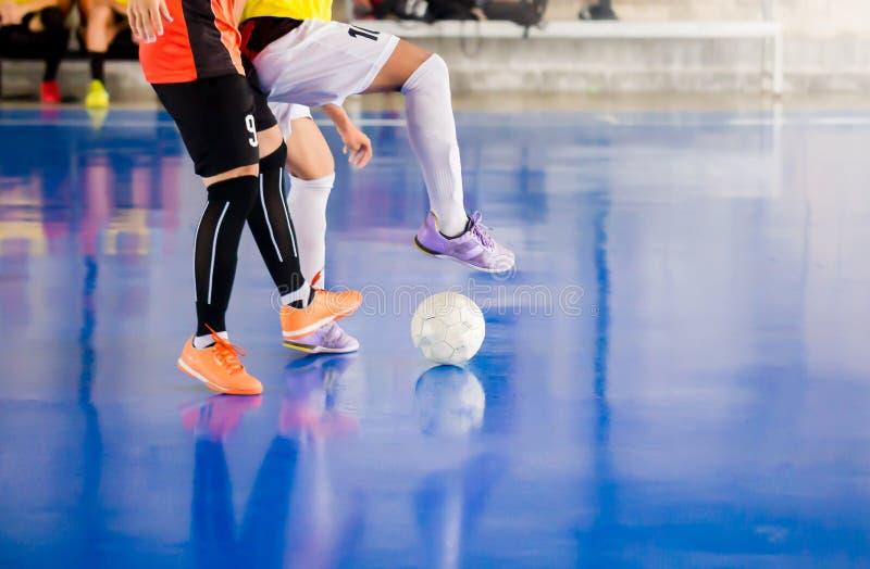 Futsal spelarefälla och att kontrollera bollen för fors till målet Fotbollspelare som slåss sig, genom att sparka bollen Inomhus  fotografering för bildbyråer