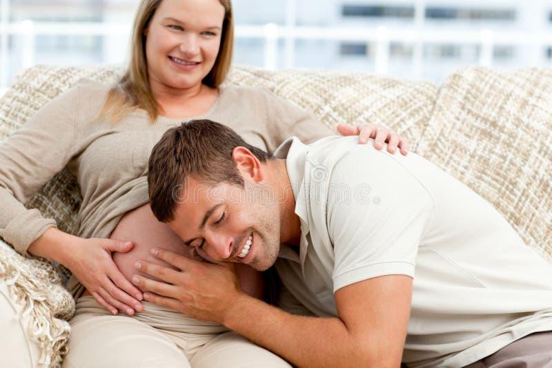 Futur papa attentif écoutant le ventre de son épouse photographie stock libre de droits