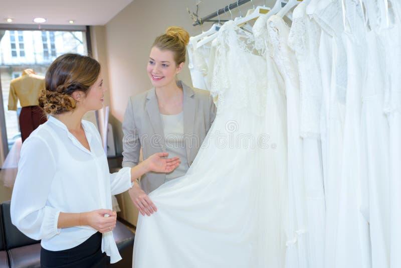 Futura esposa que hace compras para los vestidos de boda en la tienda nupcial fotografía de archivo libre de regalías