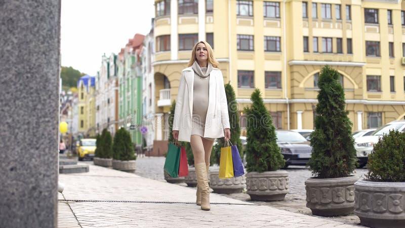 Futura mamá hermosa que camina los bolsos de compras de la calle de la ciudad, preparación del parto foto de archivo libre de regalías