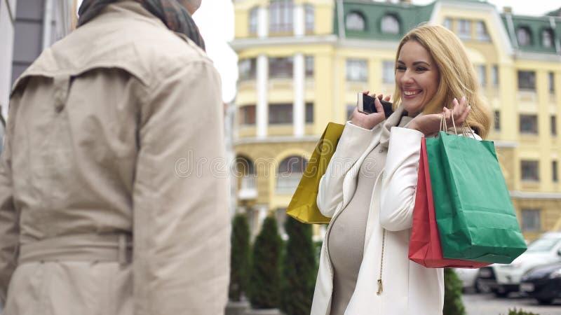 Futura mamá sonriente que muestra bolsos de compras al amigo, compra del parto, venta fotografía de archivo libre de regalías