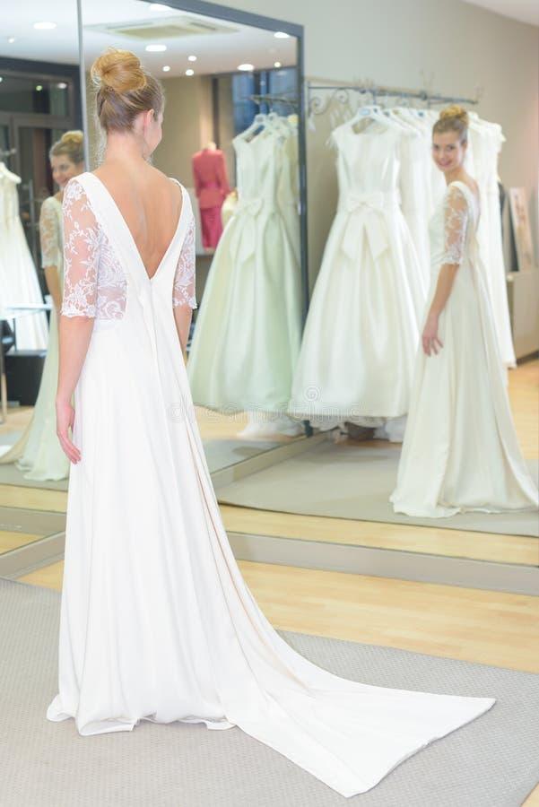 Futura sposa che prova sul vestito da sposa immagine stock
