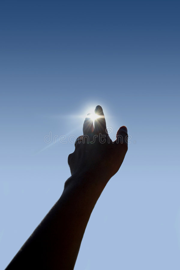 Future. A young woman is holding her hand in front of the sun