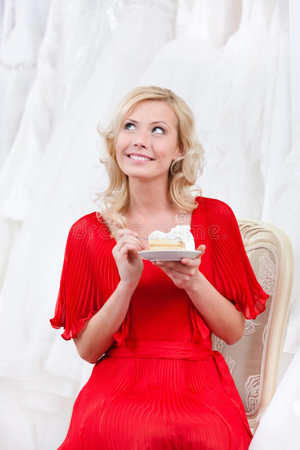 Future bride eats the wedding cake thoughtfully royalty free stock photo