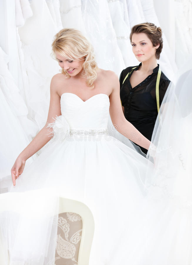 Future bride examines the dress. Girl admires the wedding dress that suits her, on white background royalty free stock photography