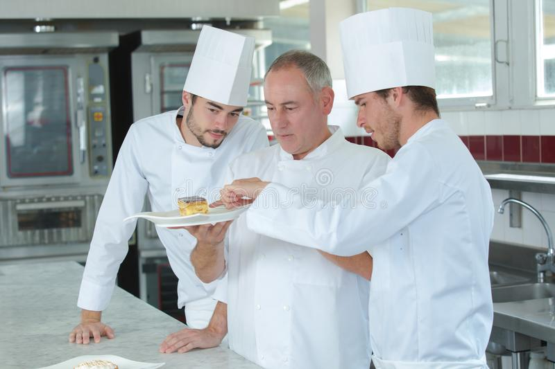 Future chefs observing presentation food. The future chefs observing the presentation of the food royalty free stock image