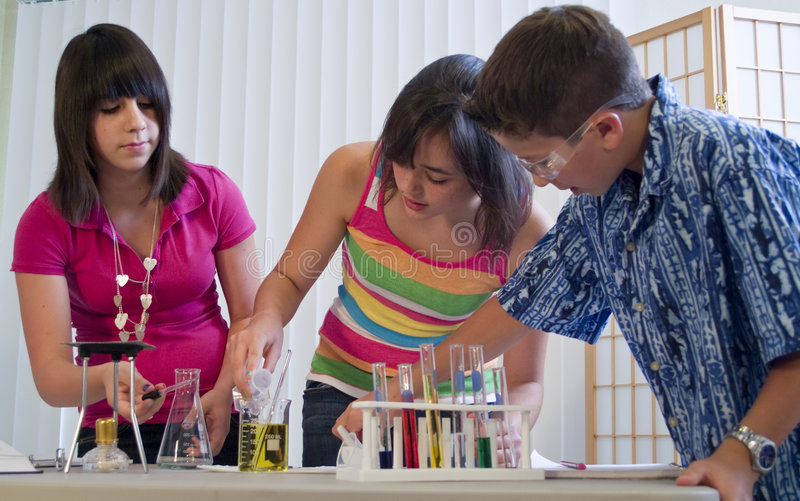 Future Chemists. Three youngsters working together on what appears to be a science or chemistry project stock image