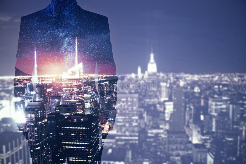 Future concept. Back view of young businessman silhouette standing on creative night city background with copy space. Future concept. Double exposure stock photos