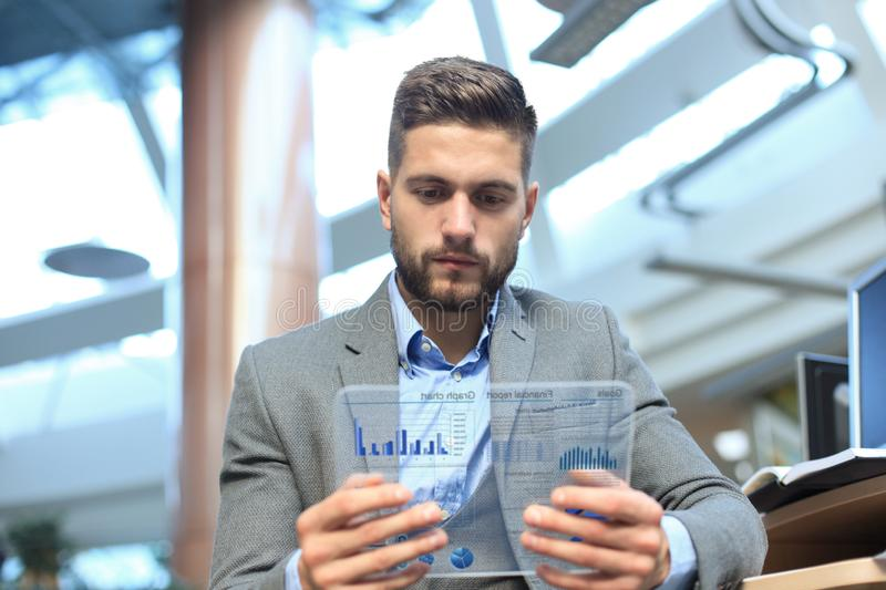 Future concept. Businessman analyzing financial statistics displayed on the futuristic transparent tablet screen. royalty free stock photo