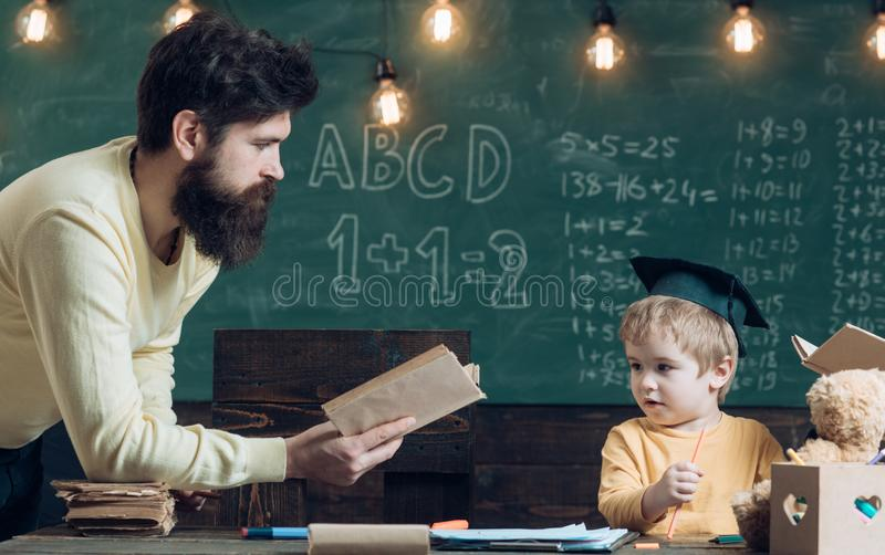 Future concept. Father teach little son to read a book, future. Future student learn reading with man teacher. Education royalty free stock photos