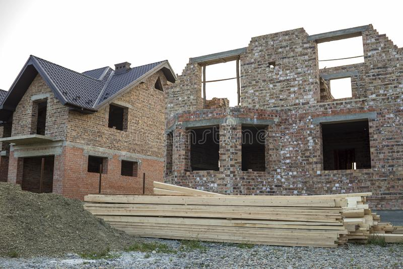 Future cottage under construction and pile of gravel and stack of boards in front of not finished new big brick house with brown s. Hingled roof. Construction stock photography
