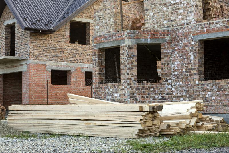 Future cottage under construction and pile of gravel and stack of boards in front of not finished new big brick house with brown. Shingled roof. Construction royalty free stock image