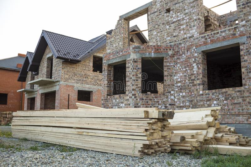 Future cottage under construction and pile of gravel and stack o. F boards in front of not finished new big brick house with brown shingled roof. Construction royalty free stock photo