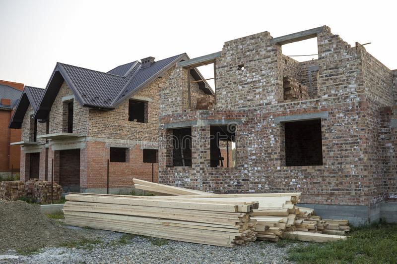 Future cottage under construction and pile of gravel and stack o. F boards in front of not finished new big brick house with brown shingled roof. Construction stock photography