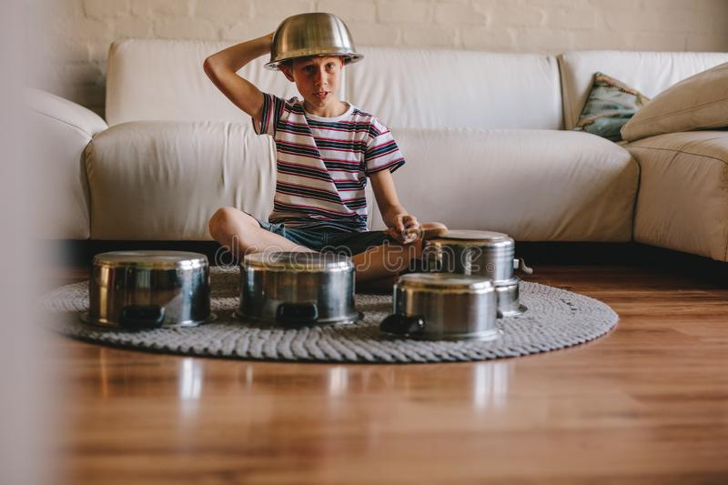 Future drummer boy with cooking pots at home. Future drummer boy wearing a bowl on the head sitting on the floor and playing on saucepans like a drummer. Boy royalty free stock photos