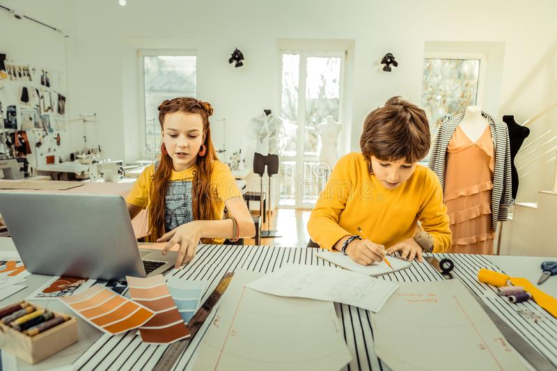 Future fashion designers working in the atelier of their mother royalty free stock image