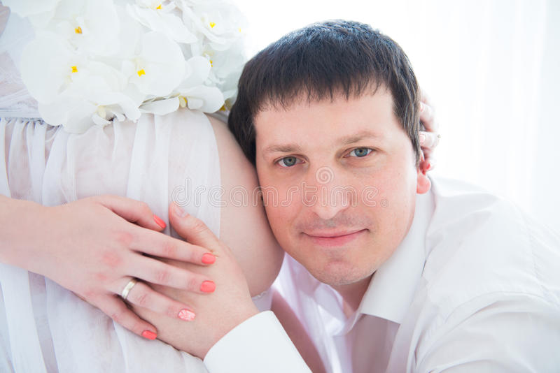 Future Happy dad hugging pregnant belly, close-up portrait stock photo