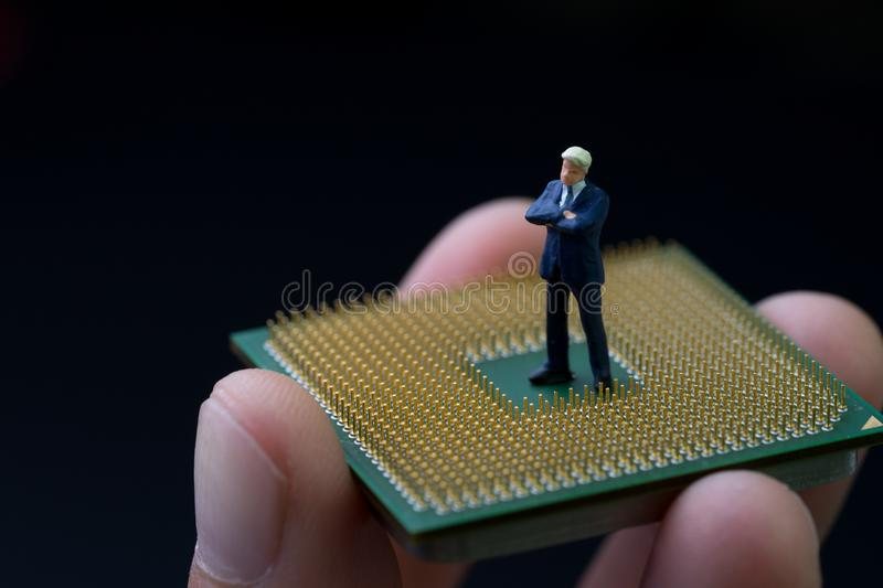 Future of human, smart artificial intelligent, AI concept, miniature figure businessman standing on computer chip in real human h. And with dark black background stock images