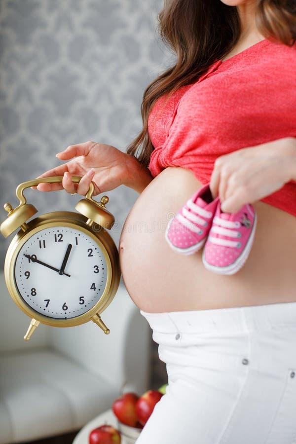 Future mère heureuse avec des butins roses à disposition photos stock