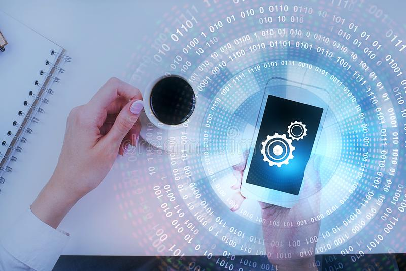Future and media concept. Top view of female hands using smartphone with cogs and digital business hologram on white office desk with coffee cup and supplies royalty free stock photo